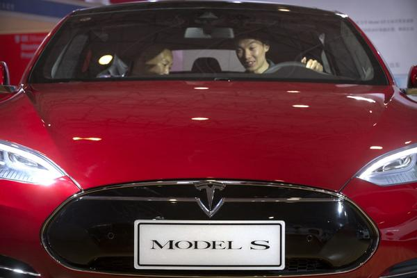"A man sits behind the steering wheel of a Tesla Model S electric car on display at the Beijing International Automotive Exhibition in Beijing on April 25, 2016. Federal officials say the driver of a Tesla S sports car using the vehicle's ""autopilot"" automated driving system has been killed in a collision with a truck, the first U.S. self-driving car fatality. T (AP Photo/Mark Schiefelbein, File)"